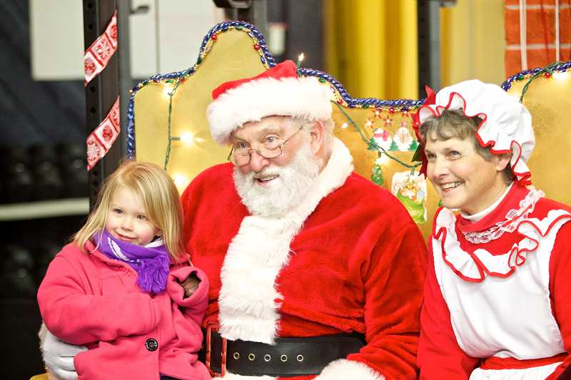 by: TIMES PHOTO: JAIME VALDEZ - Scarlett Wiley, 3, takes a picture with Santa and Mrs. Claus after telling them she would like a rocket ship for Christmas.