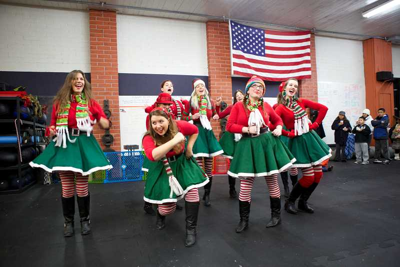 by: TIMES PHOTO: JAIME VALDEZ - The Portland Sugar Plum Elves perform for the crowd at CrossFit P.A.W. fitness following the Tigard Tree Lighting on Friday night.
