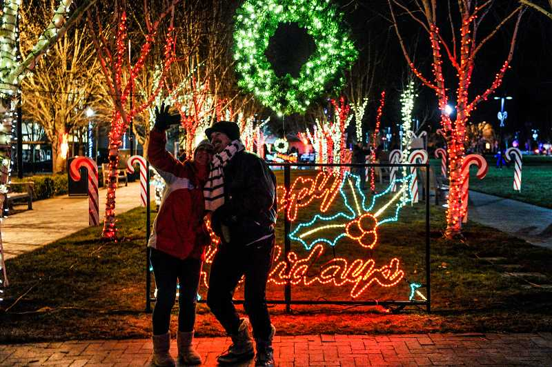 by: TIMES PHOTO: JOHN LARIVIERE - Monika Hughes and Mike Bochsler take a photo of themselves in front of the light display at Candy Cane Lane in Beaverton City Park.