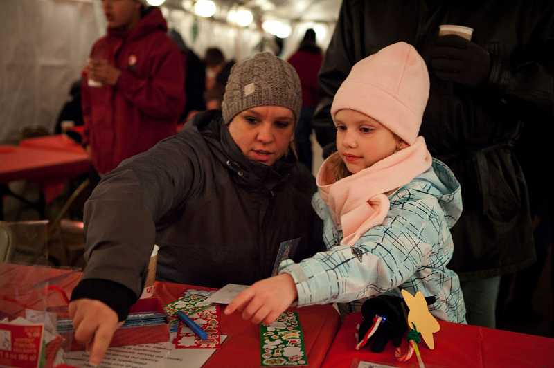 by: TIMES PHOTO: ADAM WICKHAM - Megan Vanvalkenburg, 7, (right) and her mother Kristie work on holiday cards to send to troops during the Tualatin Starry Nights and Holiday Lights Festival.