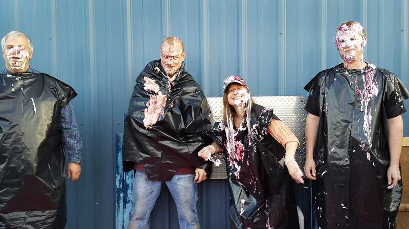 by: CONTRIBUTED PHOTO - CEO Eric Sale, left, and Beavers team leaders Jeff Loomis, Christie Licari and Myron Weirich are good sports, taking pies in the face for losing the food drive competition.