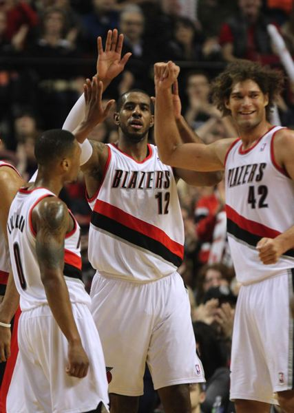 by: TRIBUNE PHOTO: JONATHAN HOUSE - LaMarcus Aldridge (center) celebrates another Blazers victory with teammates Damian Lillard (left) and Robin Lopez.