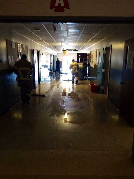 by: SUBMITTED PHOTO - Firefighters with the Scappoose Rural Fire District help clean up flooding in the schools halls Saturday, Dec. 7.