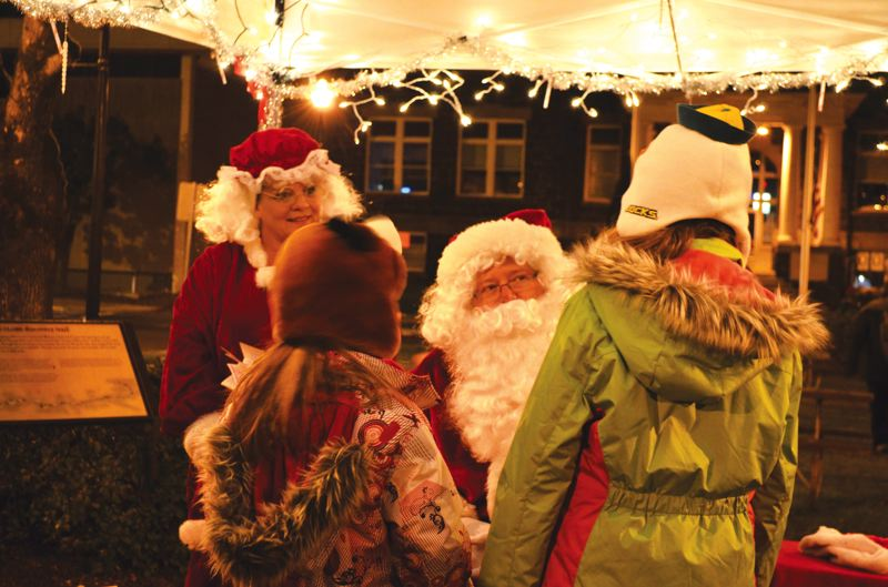 by: CITY OF ST. HELENS COURTESY PHOTO - Santa Claus (Joe Burks) and Mrs. Claus (Linda Chval) meet children at St. Helens Christmas tree lighting ceremony Saturday, Dec. 7.