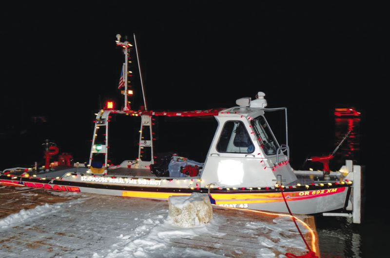 by: OREGON FIRST COURTESY PHOTO - A Scappoose Rural Fire District boat decked out with lights as part of the Christmas Ships Parade, at the end of an icy dock Saturday, Dec. 7.