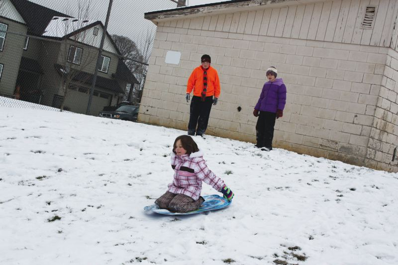 by: SPOTLIGHT PHOTO: ROBIN JOHNSON - Fifth-grader Dalton (top left), sixth-grader Kyah  (top right), and  fourth-grader Hayden (sledding) spent a portion of their snow day Monday, Dec. 9, sledding down a slope at Scappoose Middle School.
