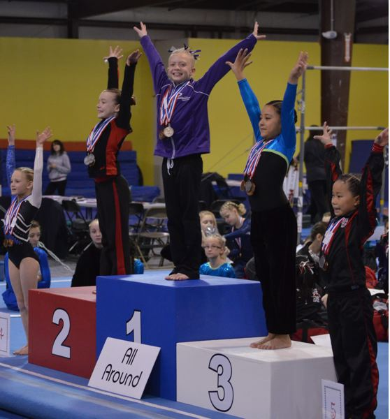 by: SUBMITTED - Oregon City nine-year-old Katelyn Hixson (center) celebrates winning gold at the 2013 Fall Compulsory State Gymnastics Championships.