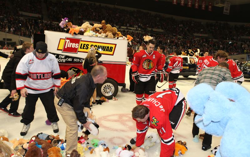 by: COURTESY OF PORTLAND WINTERHAWKS - Winterhawks players and work crew help pick up the 11,862 stuffed animals thrown onto the ice at Memorial Coliseum during last Saturday's annual Teddy Bear Toss game, won 5-3 by Portland over Seattle.