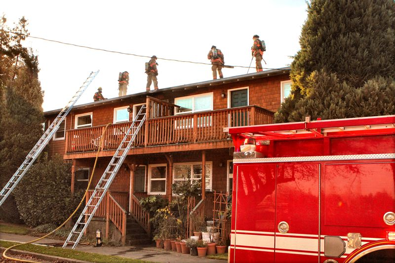 by: DAVID F. ASHTON - Firefighters get ready to cut open the roof with a chainsaw, to fight the fire in the attic.