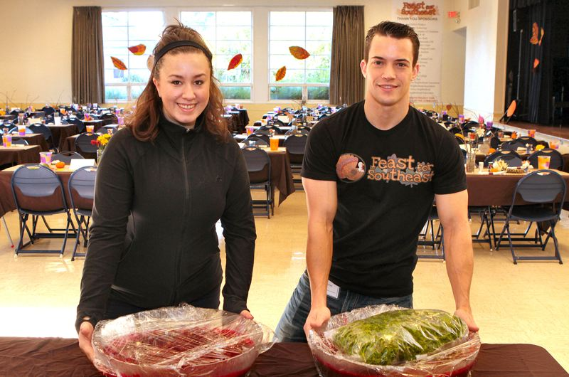 by: DAVID F. ASHTON - In the 2013 Feast for Southeast dining room, Taylor Wideman and Sam Coy bring in salads and cranberry sauce.