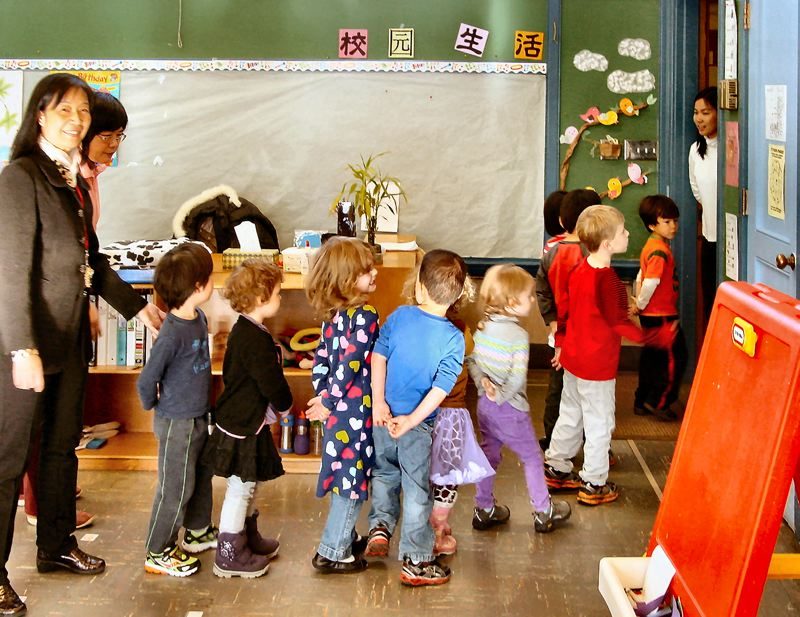 by: MERRY MACKINNON - Woodstocks Yu Miao Chinese Immersion Schools Administrator, Terry Yang, guides three- and four-year-old children through the classrooms for a break. Children enrolled in the preschool learn Chinese culture and basic Mandarin vocabulary, pronunciation, and writing.