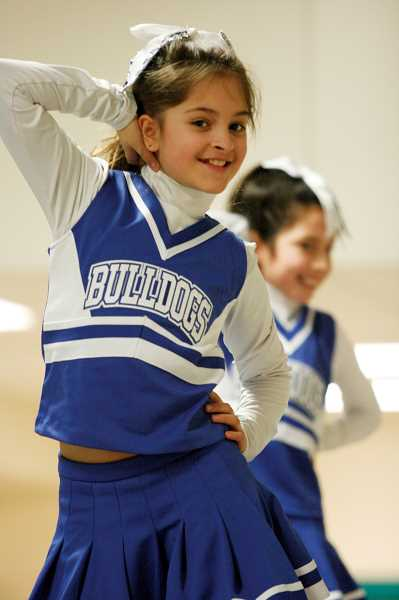 by: PHIL HAWKINS - Yesenia Lopez (front) and Isabel Vergara hold a pose during practice for the Junior Bulldogs' competitive cheer team.