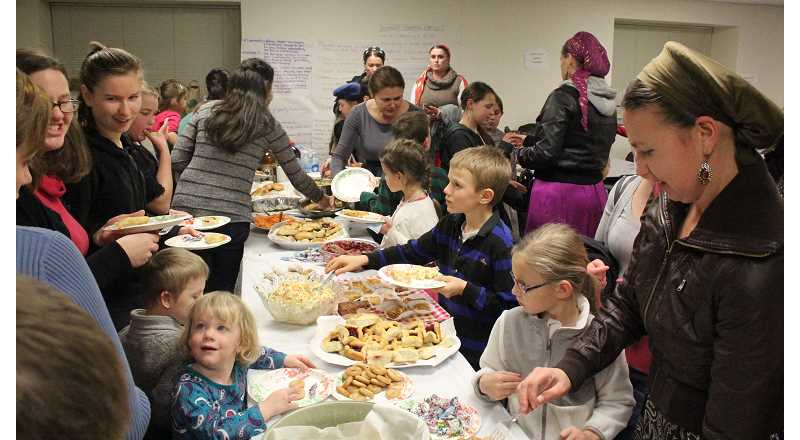 by: MAYGAN BECKERS - Heritage Elementary students and parents gather and serve a plate of Russian food after presenting individual presentations.