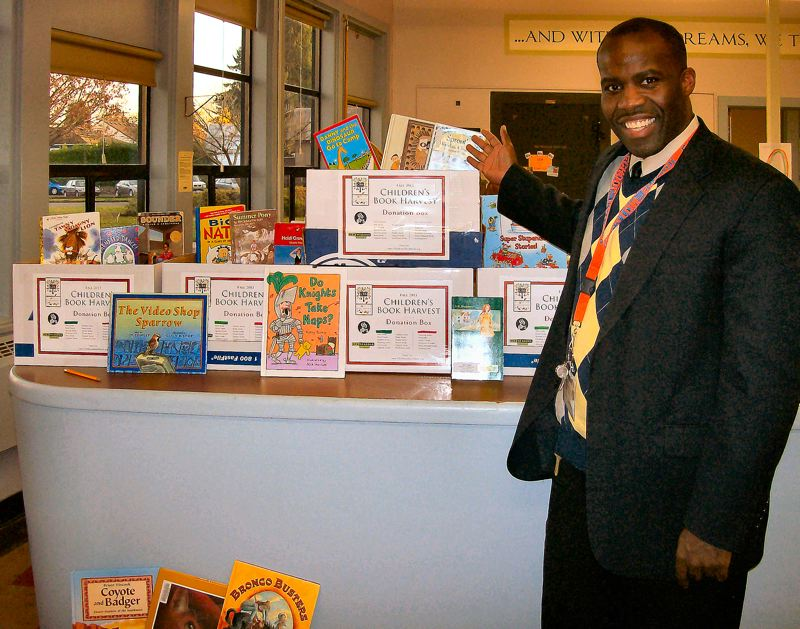 by: RITA A. LEONARD - Creston School Principal Conrad Hurdle shows some of the many books that were recently donated during their first Childrens Book Harvest.
