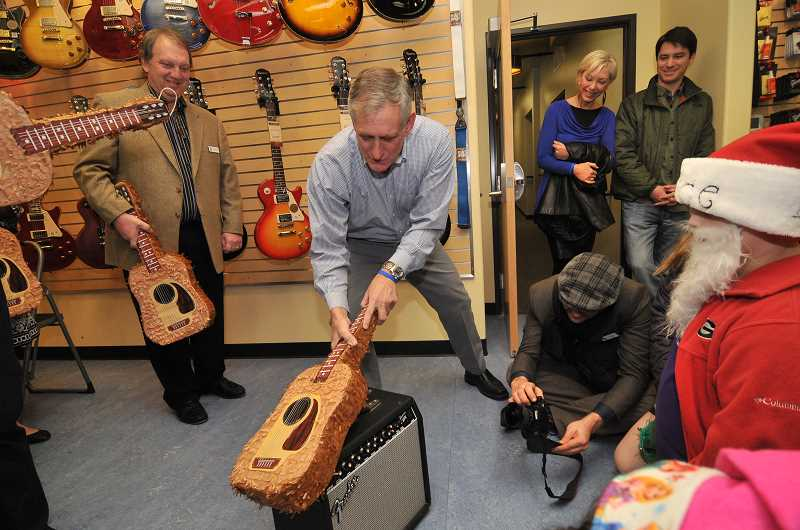 by: VERN UYETAKE - Portland Mayor Charlie Hales smashed a candy-filled guitar pinata Saturday during the grand opening of the Youth Music Project store.
