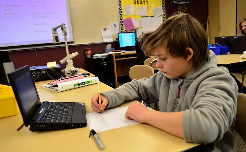 by: TIDINGS PHOTO: VERN UYETAKE - Ben Finestein writes a letter in his seventh-grade classroom at Rosemont Dec. 11