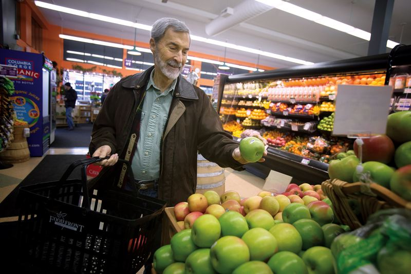 by: PAMPLIN MEDIA GROUP: JONATHAN HOUSE - James Beard Public Market director Ron Paul checks out locally sourced apples at his neighborhood grocery store, Food Front in Northwest Portland.