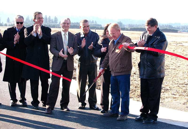 by: ISABEL GAUTSCHI - Developer Mike Park cuts the ribbon during a ceremony Wednesday, Dec. 11, at the Estacada Industrial Campus. Joining him are, from left, Business Oregon Director Tim McCabe, Estacada Mayor Brent Dodrill, Clackamas County Commissioner Paul Savas, State Rep. Bill Kennemer and State Sen. Alan Olsen.