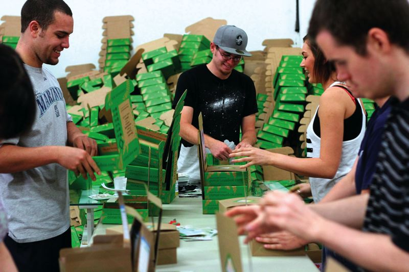 by: PAMPLIN MEDIA GROUP: JONATHAN HOUSE - Temporary employees fill Conscious Boxes with green-themed goods.