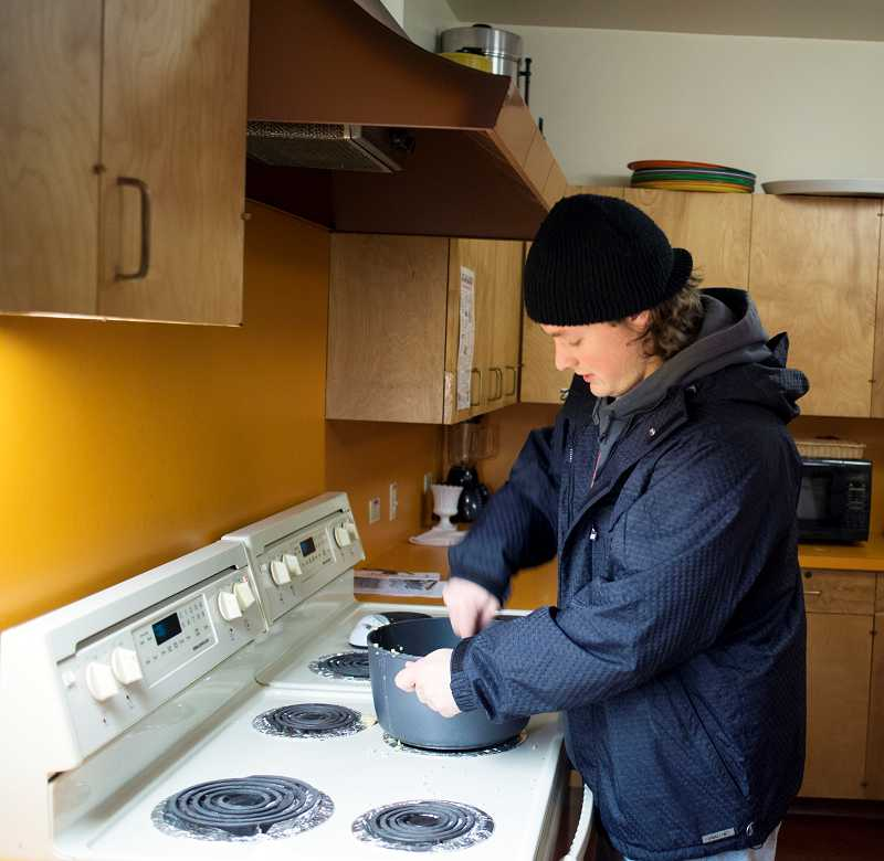 by: NEWS-TIMES PHOTO: CHASE ALLGOOD - Severe-weather shelter staff member Shane Feuerbach prepares soup for those staying in the shelter.