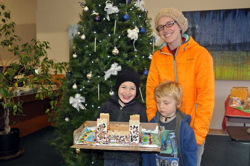 Marek Stanton (left) created a frosted graham-cracker fortress with a colored Tootsie Roll nugget dragon inside, breathing a red-frosting fire from its mouth. Brother Corban and mom Kalika look on.