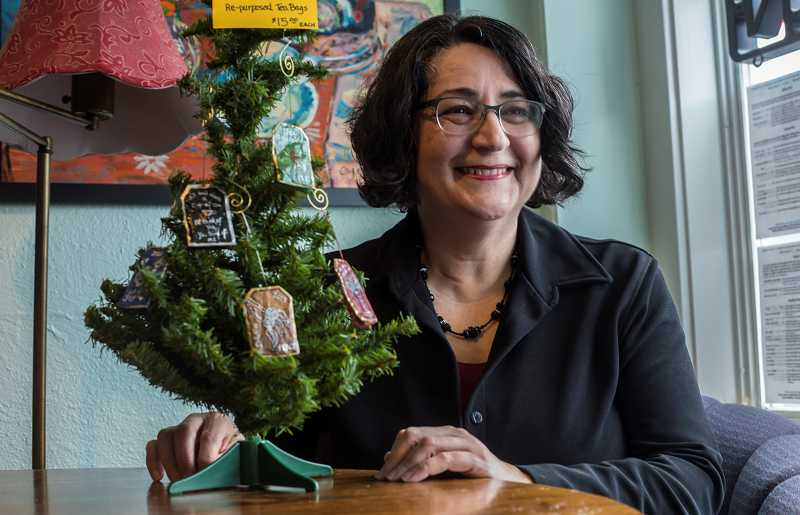 by: TIMES PHOTO: JONATHAN HOUSE - Artist Toni Curry displays a mini Christmas tree holding her tea bag ornaments at Medley Tea House in Multnomah Village.