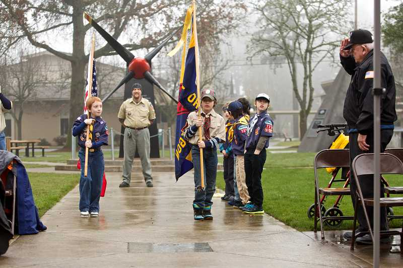 by: TIMES PHOTO: JAIME VALDEZ - Anthony Carlson, 7, and Damon Robinson, 10, carry the American flag and the pack flag to open a Wreaths Across America ceremony Dec. 14 at Beaverton's Veterans Memorial Park.