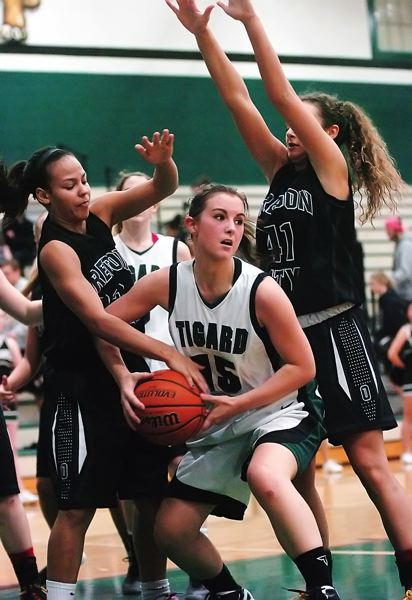 by: DAN BROOD - IN THE PAINT -- Tigard senior Jessie King (15) battles against Oregon City's Cierra Walker (left) and Taylor Shaw in Friday's game.