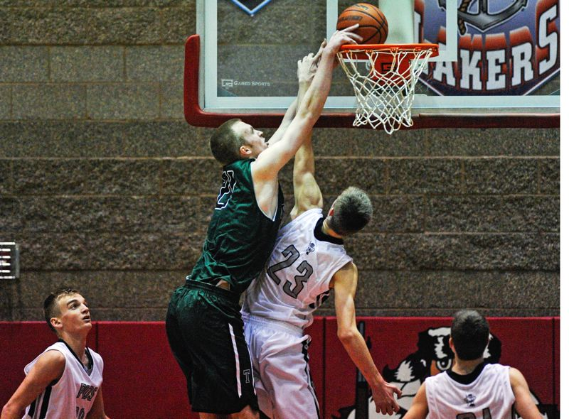 by: JOHN LARIVIERE - SLAM IT HOME -- Tigard junior post Joel Johnson (left) goes up for a dunk over Oregon City's Austin DeWitz during Friday's game. The Tigers scored a 73-60 victory over the Pioneers.