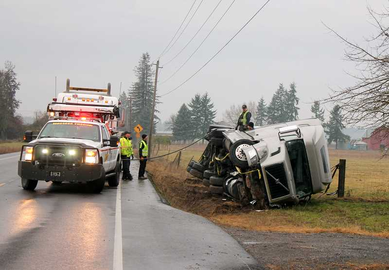 by: CORY MIMMS - A truck hauling a trailer full of aluminum rolled over just west of Molalla on Highway 211 at 5:45 a.m. Friday, Dec. 20.