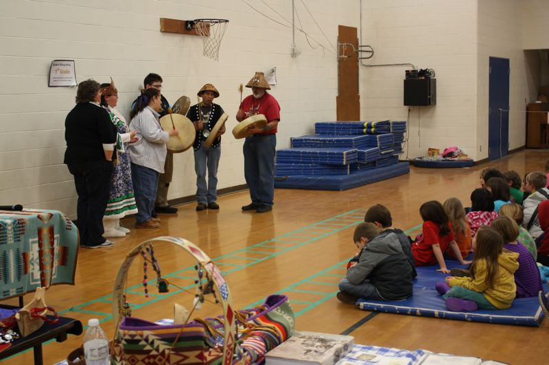 by: SPOTLIGHT PHOTO: ROBIN JOHNSON - Members of the Confederated Tribes of the Grand Ronde provide a cultural presentation to Sauvie Island Academy students, families, and area residents. The event featured tribal drumming and singing, traditional foods, paint making, cordage making and more.