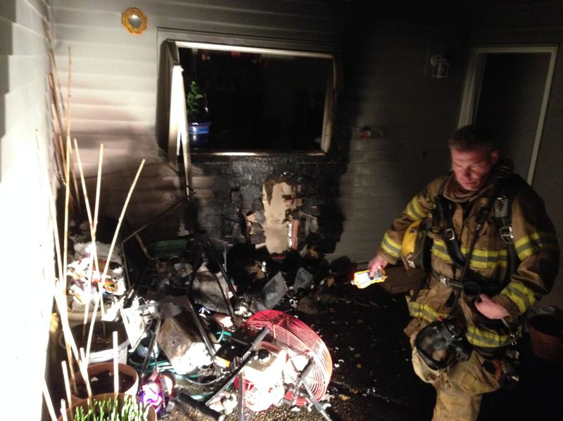 by: LAKE OSWEGO FIRE DEPARTMENT - A firefighter emerges from a Lake Oswego home that caught fire early Monday morning.