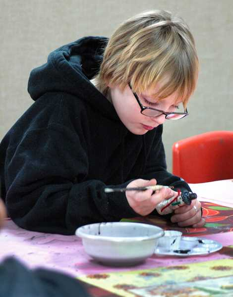 by:  ISABEL GAUTSCHI -  Trask Ault puts some finishing touches on his snowman.
