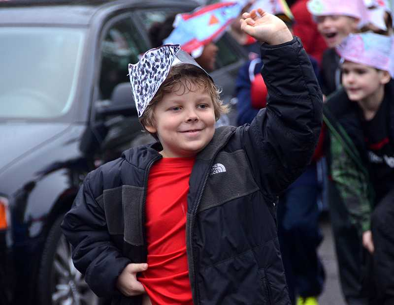by: TIDINGS PHOTO: VERN UYETAKE - Third-grader Zachary Liston waves during the parade Dec. 19.
