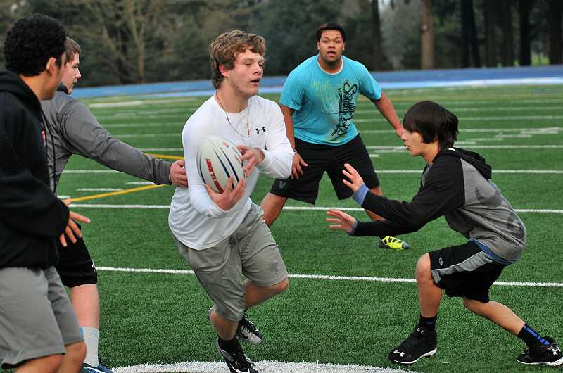 by: REVIEW PHOTO: VERN UYETAKE - Jake Moser tries to avoid Jacob Gordon as he runs the ball during a Lakeridge High rugby team practice on Thursday.
