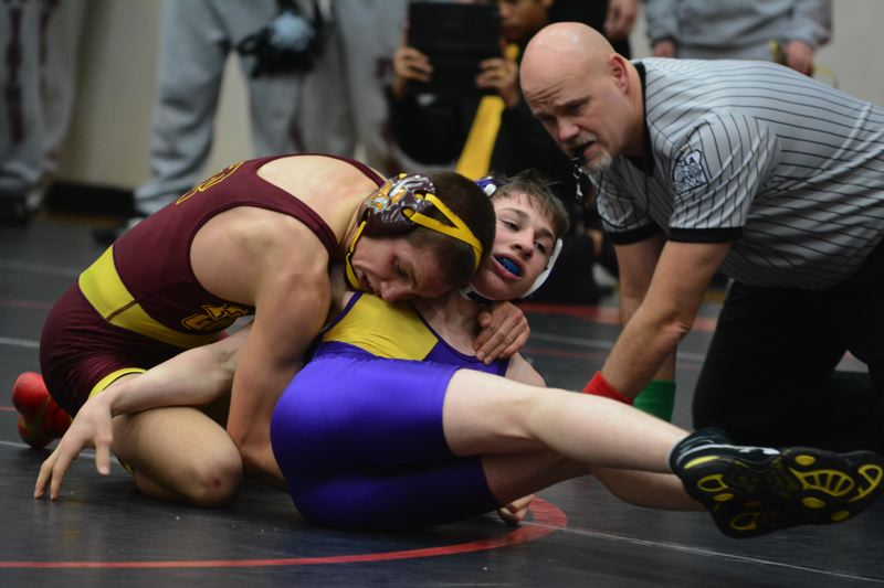by: TIMES PHOTO: MATT SINGLEDECKER - Sunset 120-pound wrestler Zachary Morello tries to fight off a Forest Grove foe in the first period of Morello's match on Wednesday.