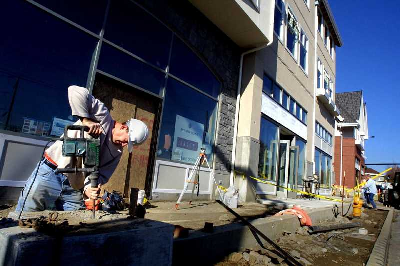 by: FILE PHOTO - Tom Taggart of R&H Construction uses a hammer drill in November 2003 to fix a point in the poured concrete at Lakeview Village, a new retail and commercial center in Lake Oswego.