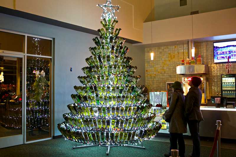 by: TIMES PHOTO: JAIME VALDEZ - Moviegoers at Progress Ridge Cinetopia marvel at the unique wine-bottle Christmas tree in the theater's lobby. Frank Emmert, owner of Emmert Fabricators in Tigard, created the tree.