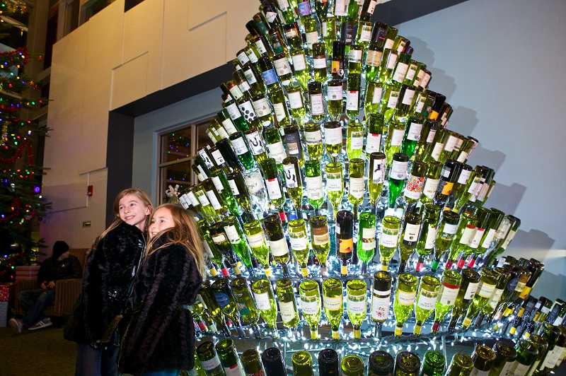 by: TIMES PHOTO: JAIME VALDEZ - Halle Sheldon, 8, and Maddie Schatzman, 8, have their picture taken by a Christmas tree made of wine bottles at the Progress Ridge Cinetopia.