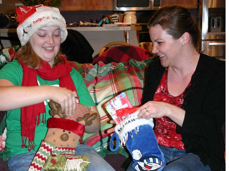 by: JASON CHANEY - Jessica Hudspeth (LEFT) and Kristy Reynolds (RIGHT) prepare stockings for their entire family every Christmas Eve. The tradition also includes an annual shopping trip to purchase all of the stocking stuffers.
