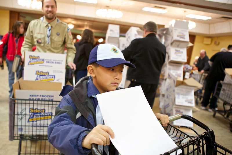by: TIMES PHOTO: JAIME VALDEZ - Logan Faulkner, 9, who is a Cub Scout with Pack 767, waits in line with his shopping cart to fill his list with food and toys for the needy at the annual Beaverton Elks Lodge Christmas Basket Delivery.