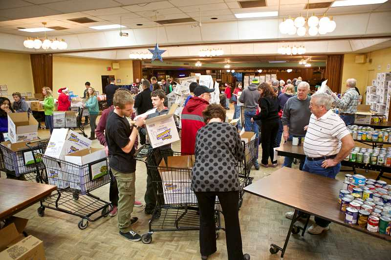 by: TIMES PHOTO: JAIME VALDEZ - Boy Scouts and volunteers line up with their shopping carts to fill them with food and toys for the needy at the annual Beaverton Elks Lodge Christmas Basket Delivery.