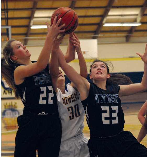 by: SETH GORDON - Woodburn's Kylie Doman (left) and Ashley Doman converge for a rebound in the Bulldogs 46-44 loss at Newberg High School Friday night.