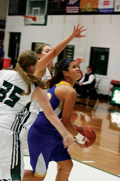 by: PHIL HAWKINS - Gervais junior Jelayna Bastidas works inside for two of her eight points in the Lady Cats' 73-37 loss at Salem Academy Thursday night.