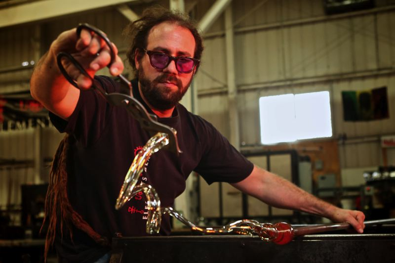 by: TRIBUNE PHOTO; JAMIE VALDEZ - Ian Gilula, co-owner of Elements Glass, has only moments to find the shape he wants before his liquid glass turns solid. This month, about 1,000 customers have come to Elements to blow their own Christmas ornaments.
