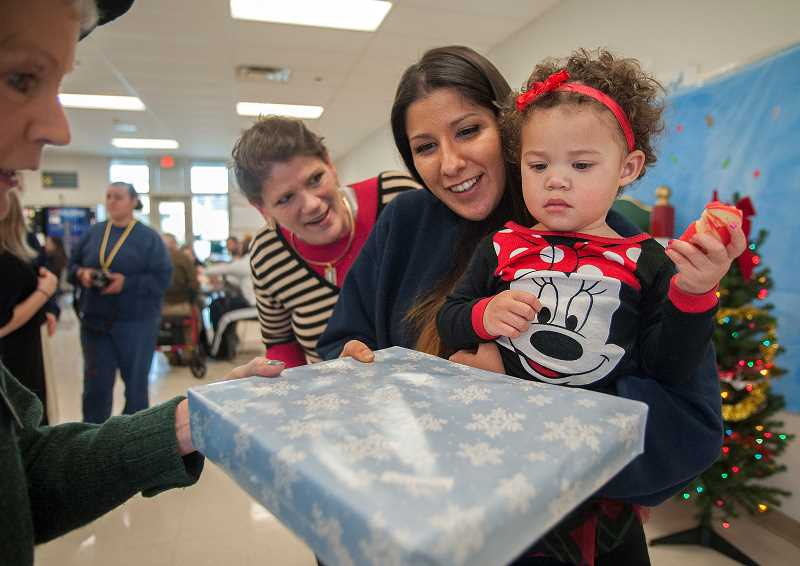 by: JOSH KULLA - Coffee Creek inmate Dez Rocha and her daughter, Ahonie Rocha-Menjivar, 2, receive a gift from volunteer elf Susie Sivyer at the winter Through a Child's Eyes event Dec. 16.