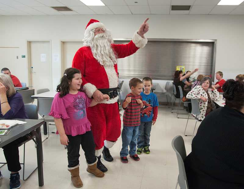 by: JOSH KULLA - Wilsonville resident and Rotary Club member John Ludlow has helped out Santa for 12 years as part of the Through a Child's Eyes effort mounted by local Rotarians. To Ludlow's right is Linsey Lesperance, 8, while Don McVay and Mike Kane dance to Santa's left.