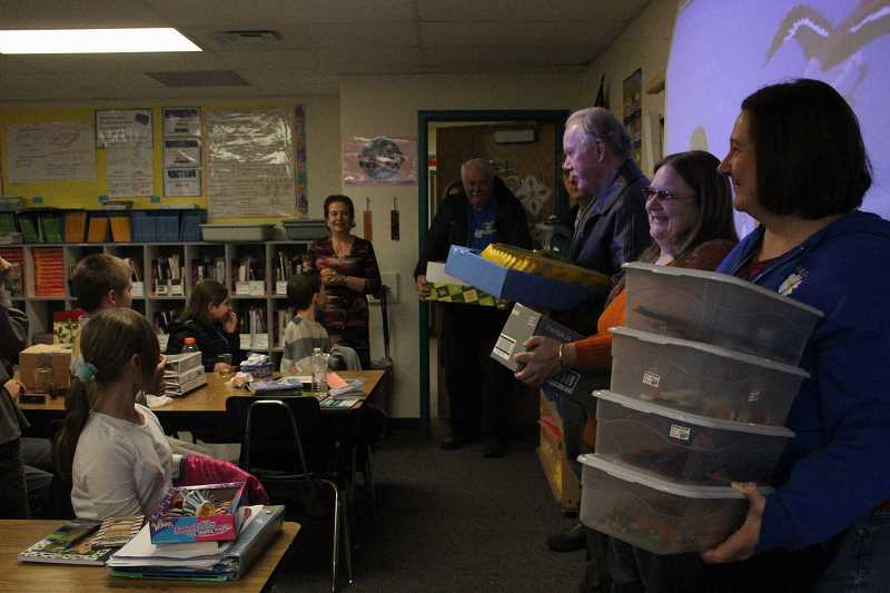 by: LINDSAY KEEFER - Kiwanians (from right) Julie Moore, Lisa Ellsworth, Jim Hendryx, Mike Bergeron and Walt Mangerich deliver supplies to Liliya Zaltsman's fifth-grade class.