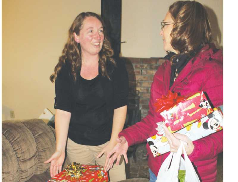 by: SUSAN MATHENY - Terri Gano, left, is surprised by a generous Christmas delivery from PGE employees, including Janis Dinkel, right.