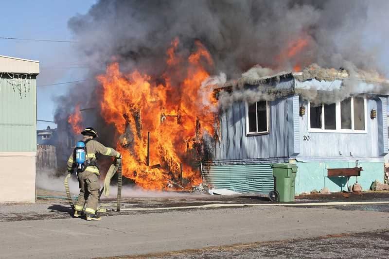 by: SUSAN MATHENY - A firefighter lays out hose for the initial attack on the mobile home fire at Tops Trailer Park on Dec. 19. The home was completely burned.